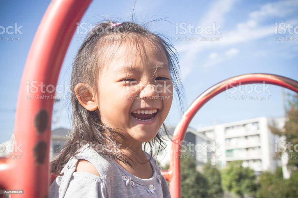 Little girl smiling at a park stock photo