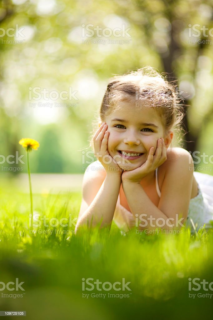 Little girl smiling at camera and resting her chin on hands royalty-free stock photo