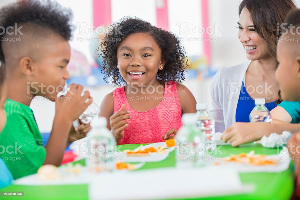 Little girl smiling at friend during snack time at daycare stock photo