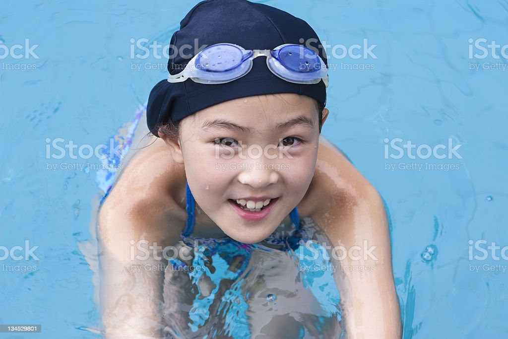 little girl smiling in swimming pool stock photo