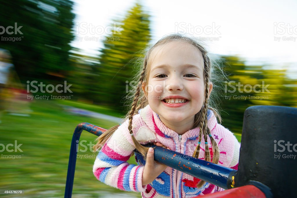 Little girl smiling on a moving merry-go-round stock photo