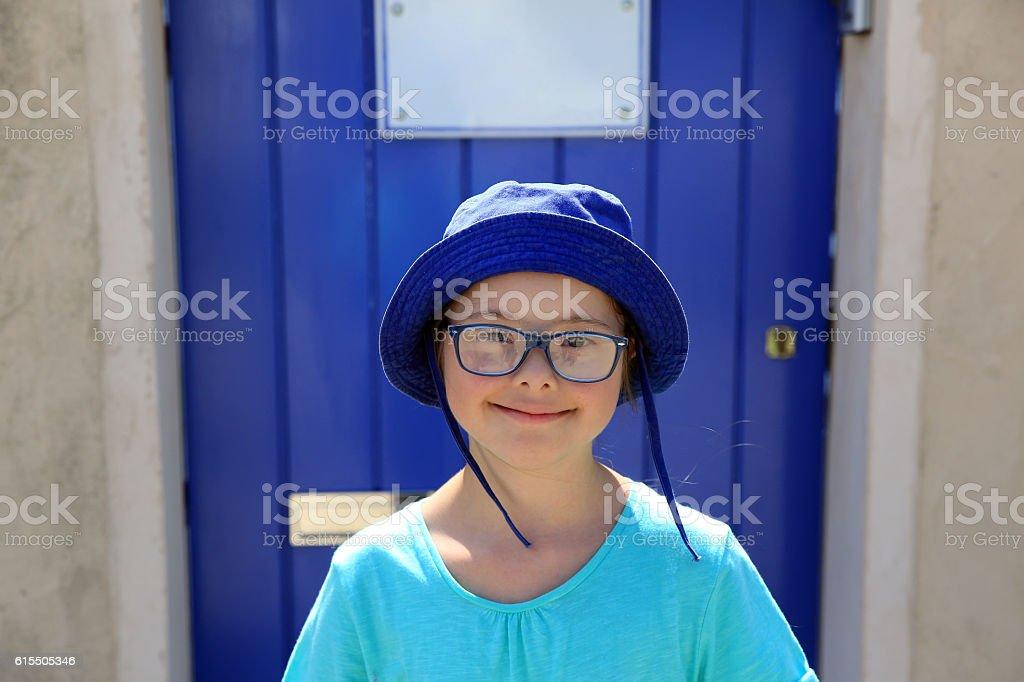 Little girl smiling on background of blue door stock photo