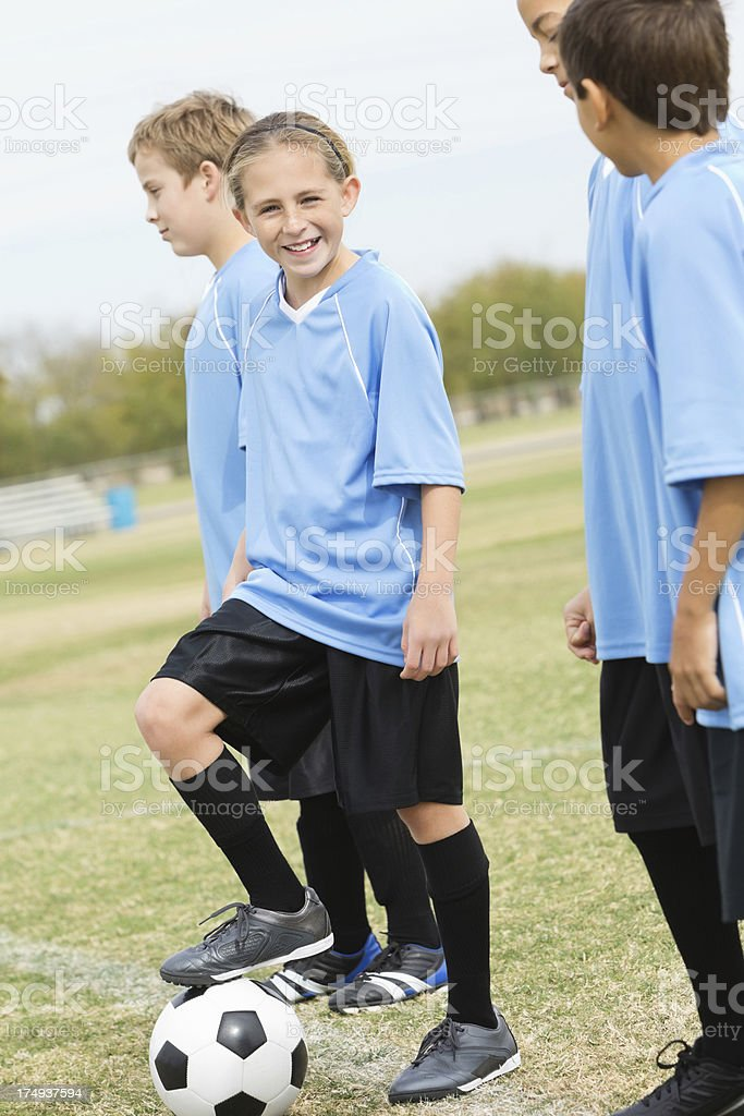 Little girl smiling on sidelines of youth soccer game royalty-free stock photo