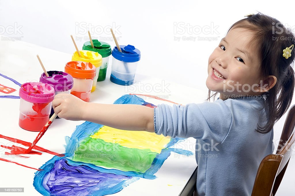 A little girl smiling while painting royalty-free stock photo