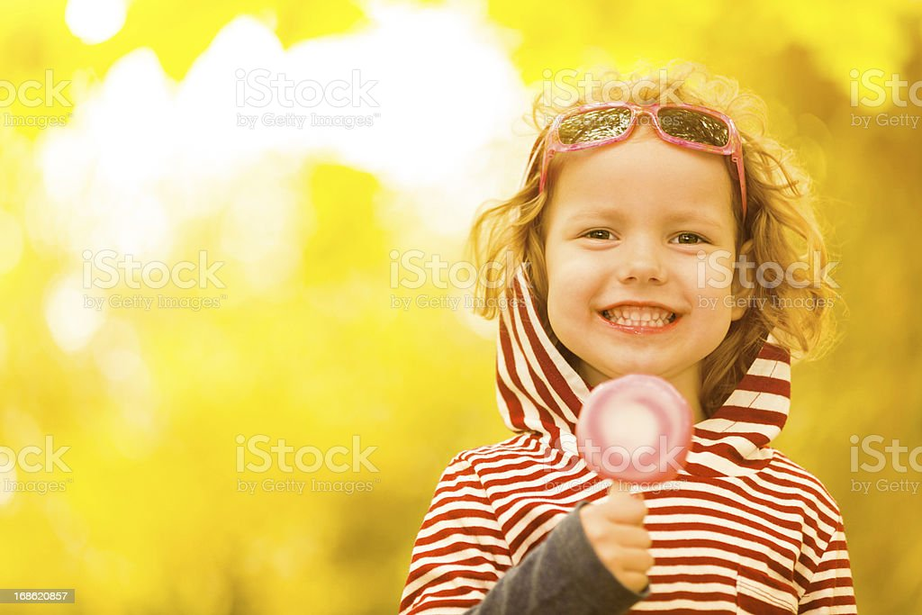 Little girl smiling with a lollipop on a yellow background royalty-free stock photo