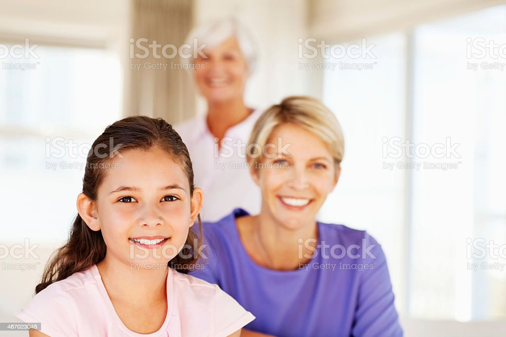 Little Girl Smiling With Grandmother And Mother In Background royalty-free stock photo