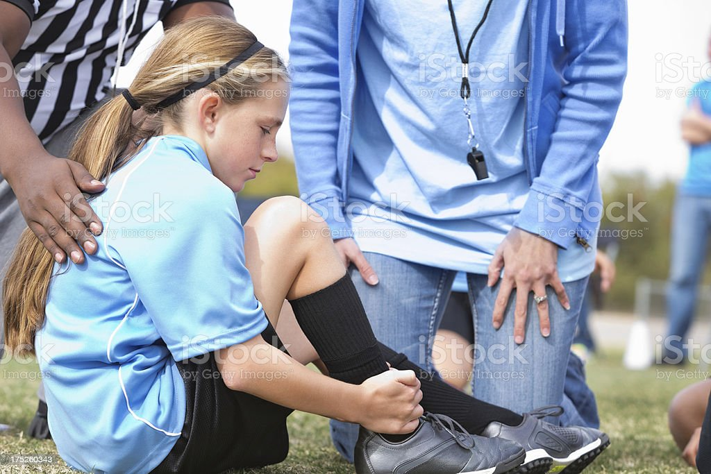 Little girl soccer player with injured ankle during game royalty-free stock photo