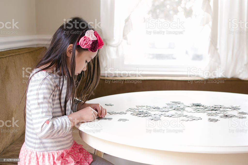 Little girl solving a jigsaw puzzle stock photo