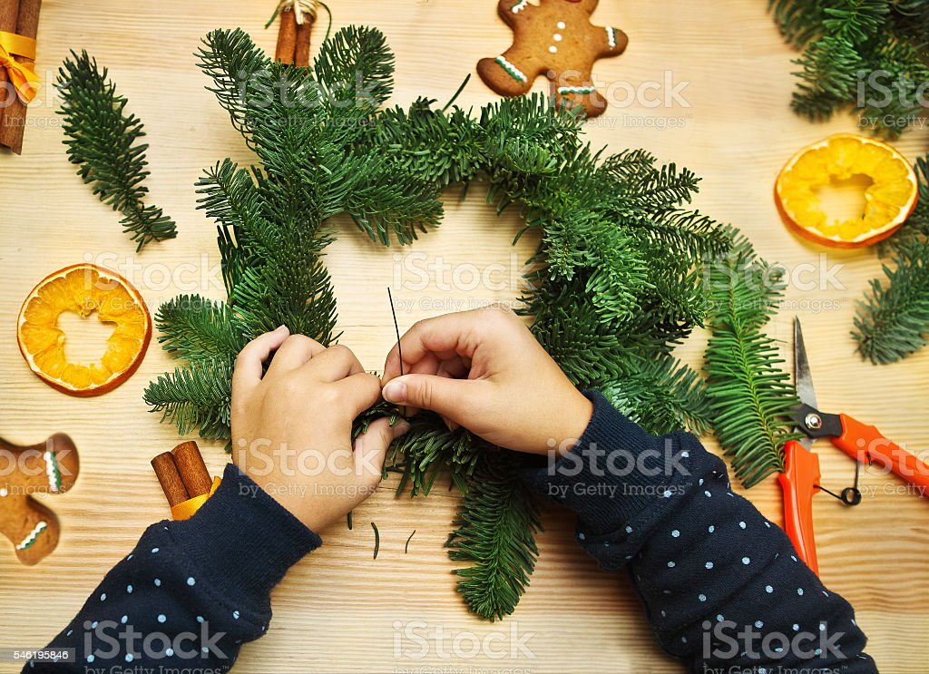 Little girl spinning and decorating Christmas wreath stock photo