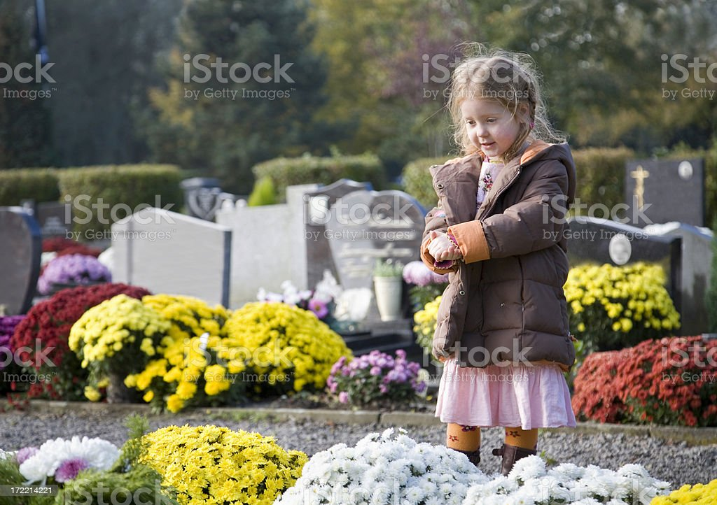 Little girl standing at a gravestone stock photo