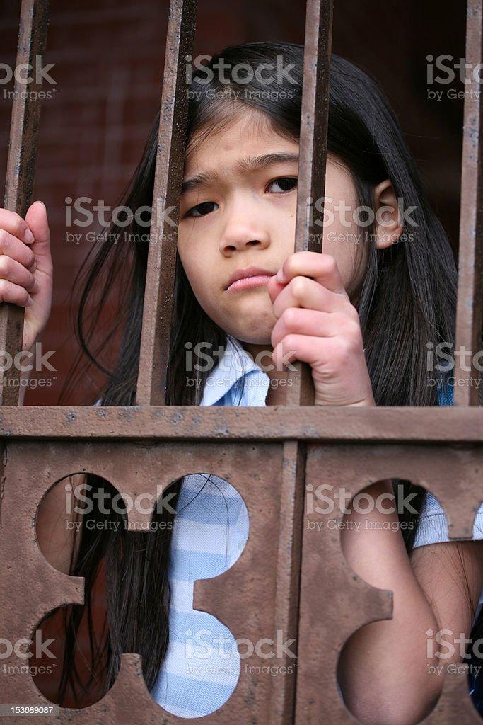 Little girl standing behind iron bars stock photo