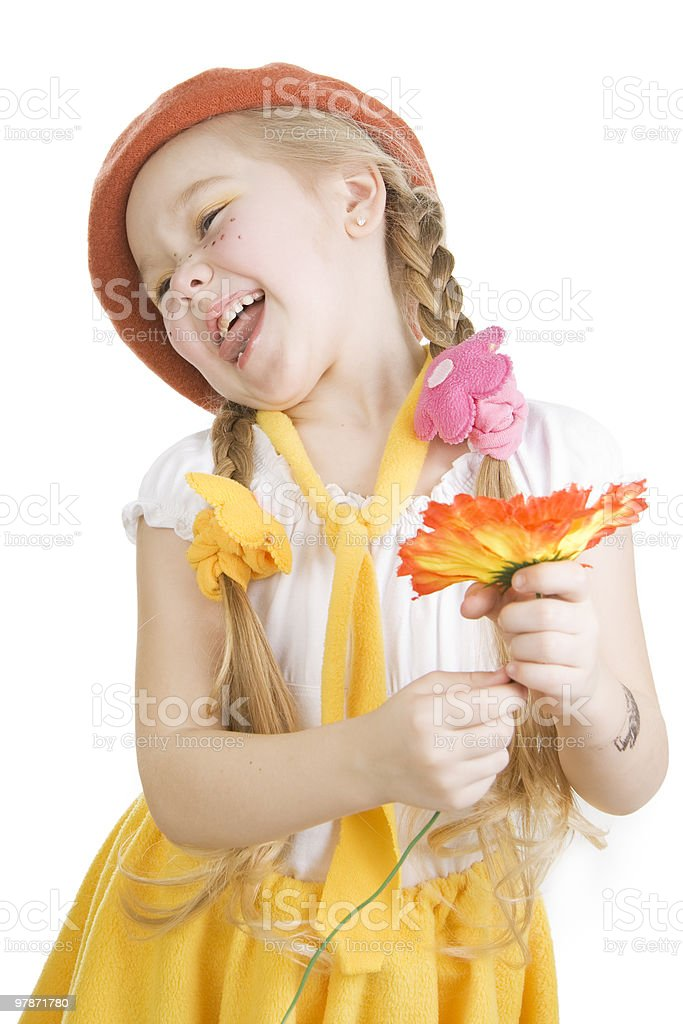 Little girl standing  holding a flower and grimacing. stock photo
