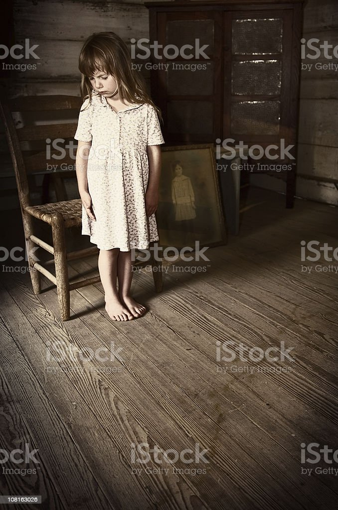 Little Girl Standing in Antique Room Near Vintage Photograph stock photo