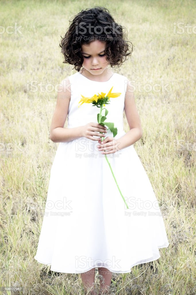 Little Girl Standing in Field and Holding Flower stock photo