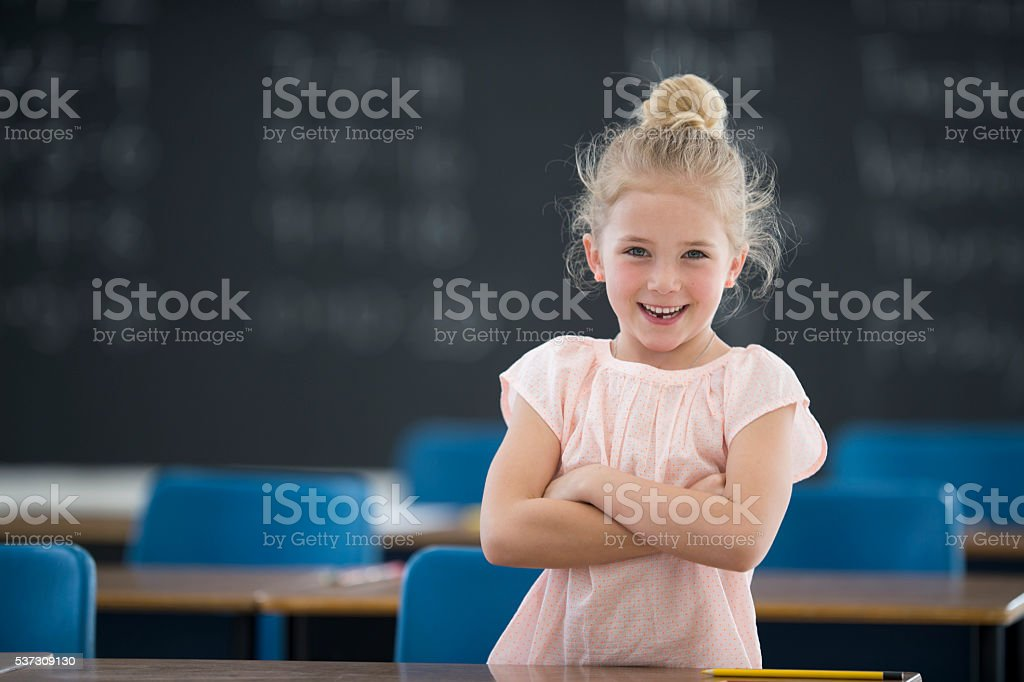 Little Girl Standing in Her Classroom stock photo