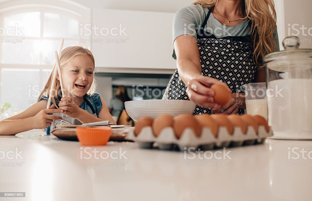 Little girl standing in kitchen with mother baking stock photo