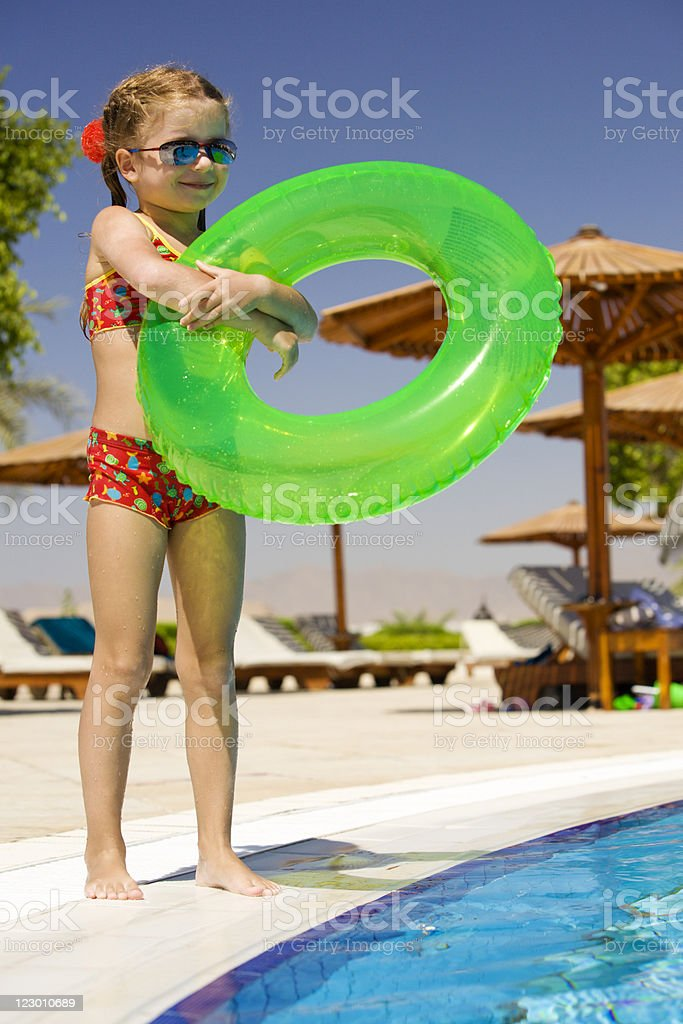 Little girl standing near pool and holding inflatable ring royalty-free stock photo