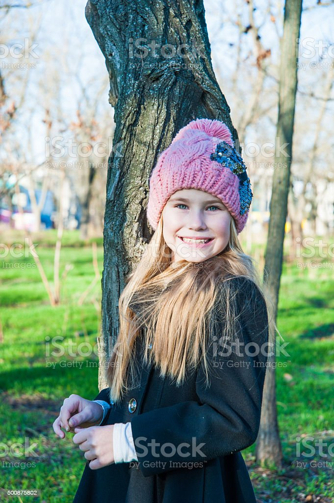 Little girl standing near tree cold season stock photo
