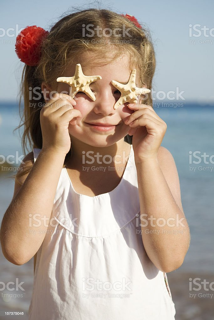 Little girl standing on beach and showing starfish royalty-free stock photo