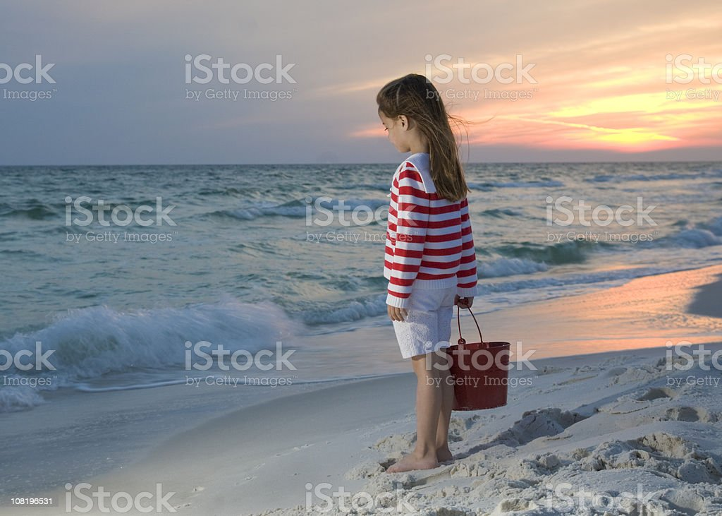 Little Girl Standing on Beach at Sunset royalty-free stock photo