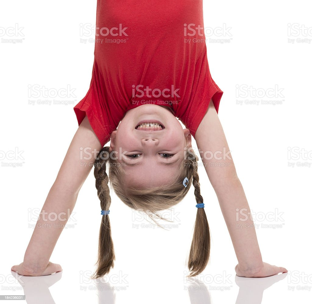 little girl standing on her hand stock photo
