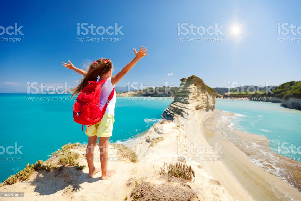 Little girl standing on rock with arms outstretched royalty-free stock photo