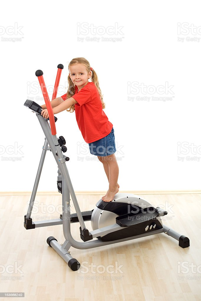 Little girl standing on top of elliptical trainer royalty-free stock photo