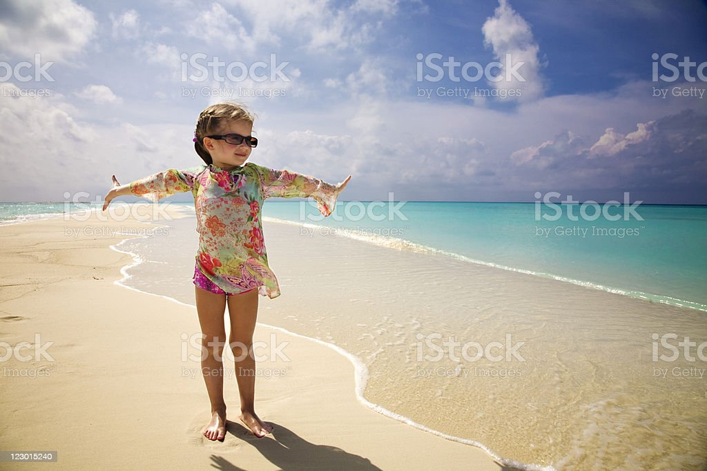 Little girl standing on tropical beach with arms outstretched royalty-free stock photo