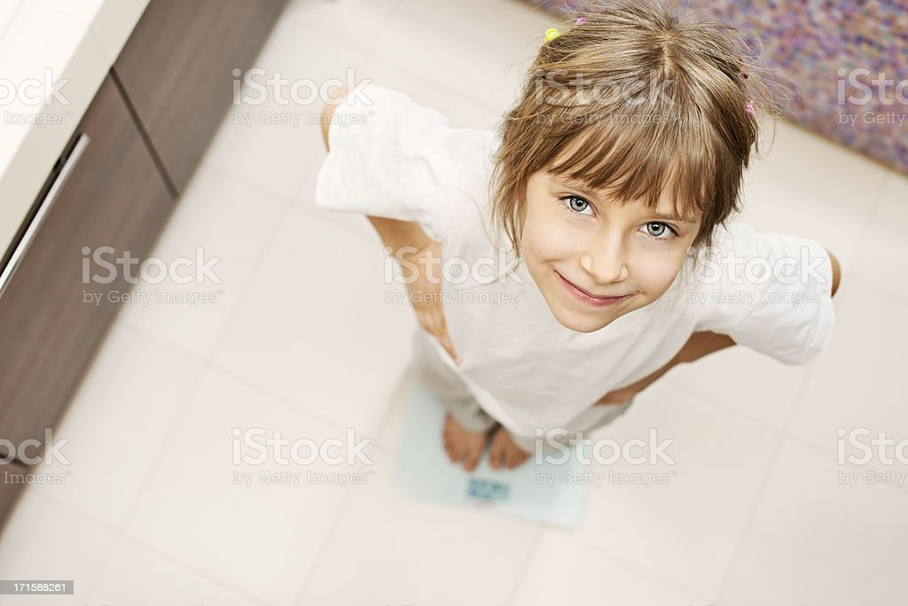 Little girl standing on weight scales royalty-free stock photo