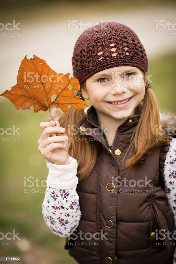 Little Girl Standing Outside on Fall Day and Holding Leaf royalty-free stock photo