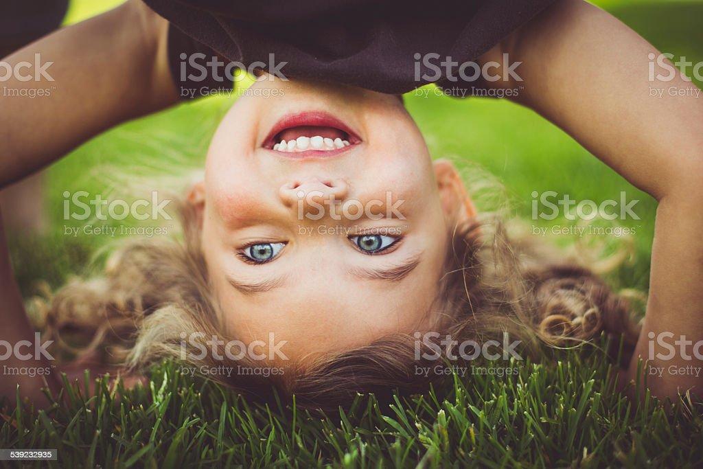 Little girl standing upside down. stock photo