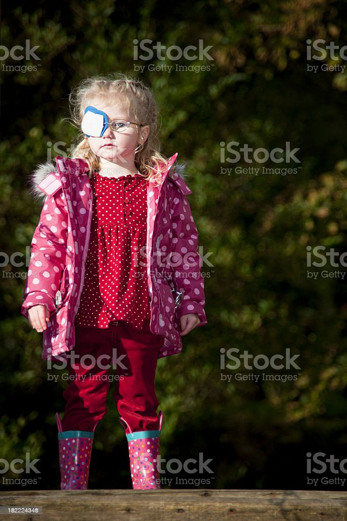 little girl standing waiting at an adveture playground royalty-free stock photo