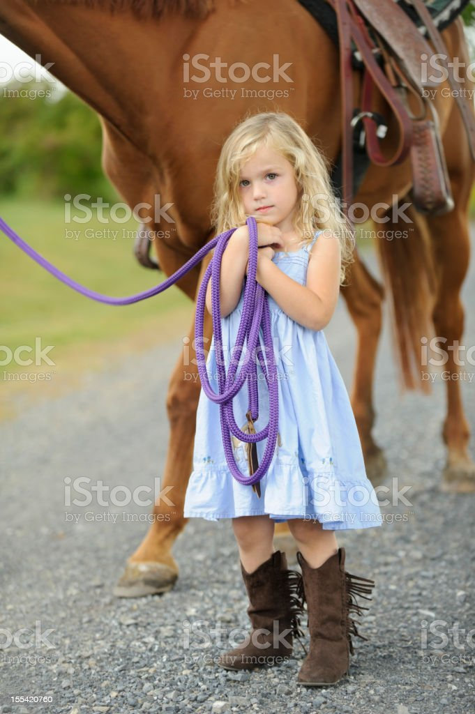 Little Girl Standing With Big Horse, Blue Dress and Boots royalty-free stock photo