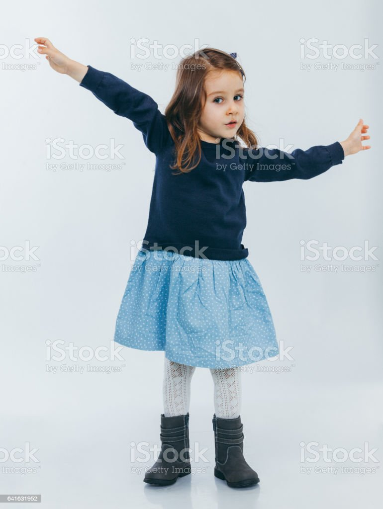 Little girl standing with hands up stock photo