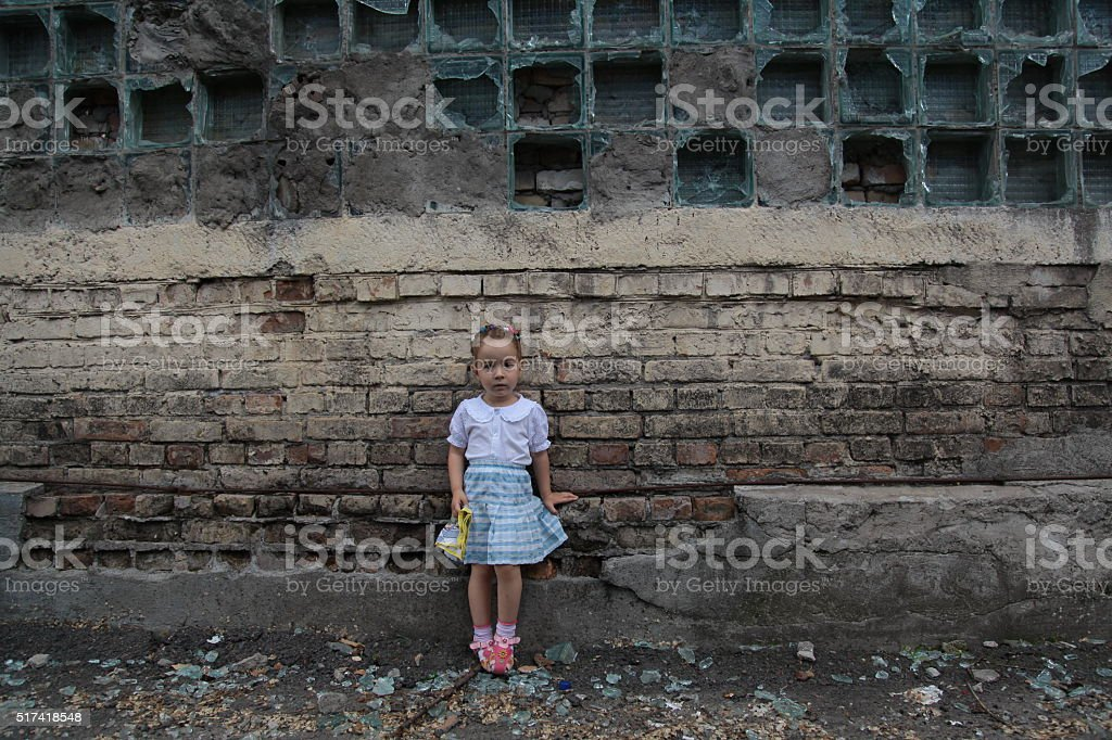 little girl stands near the destroyed wall stock photo