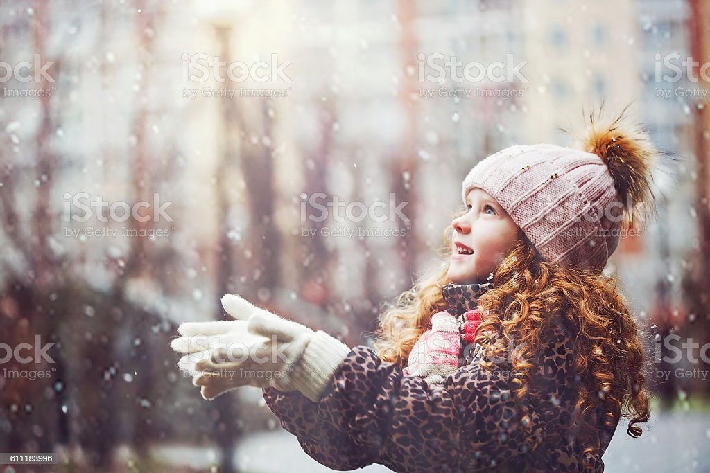 Little girl stretches her hand to catch falling snowflakes. stock photo