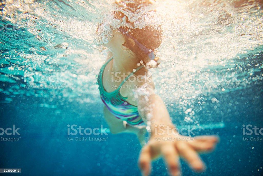 Little girl swimming crawl stock photo