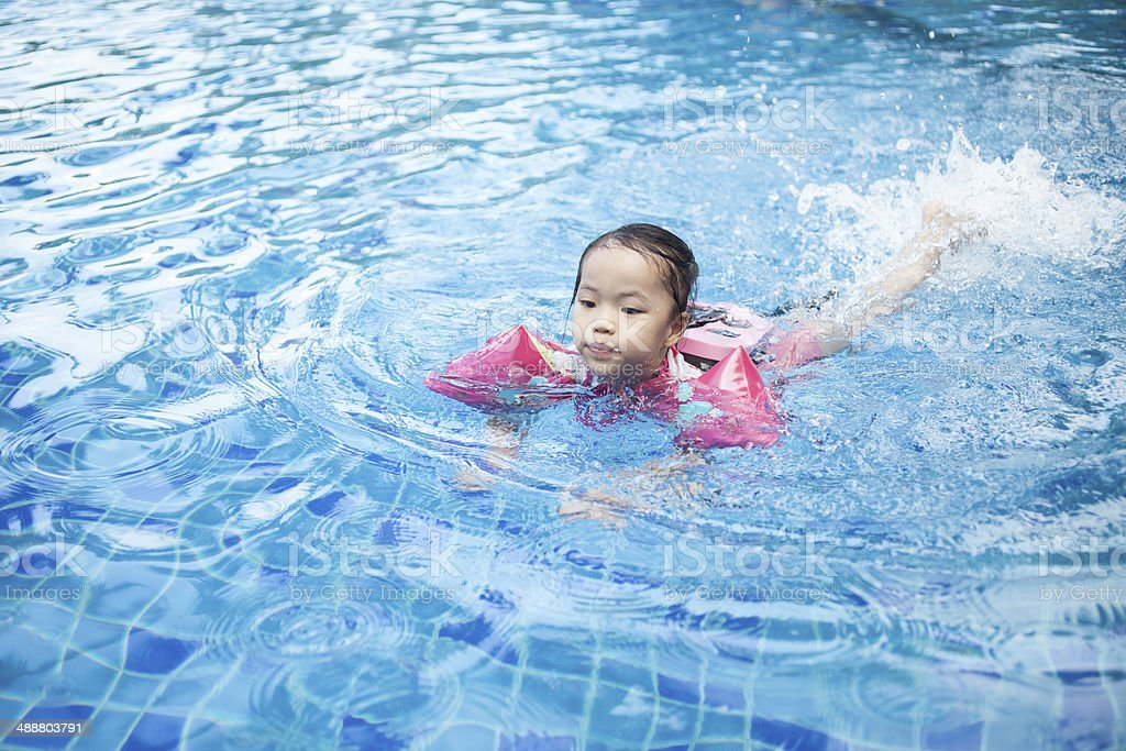 Little Girl Swimming in Action stock photo