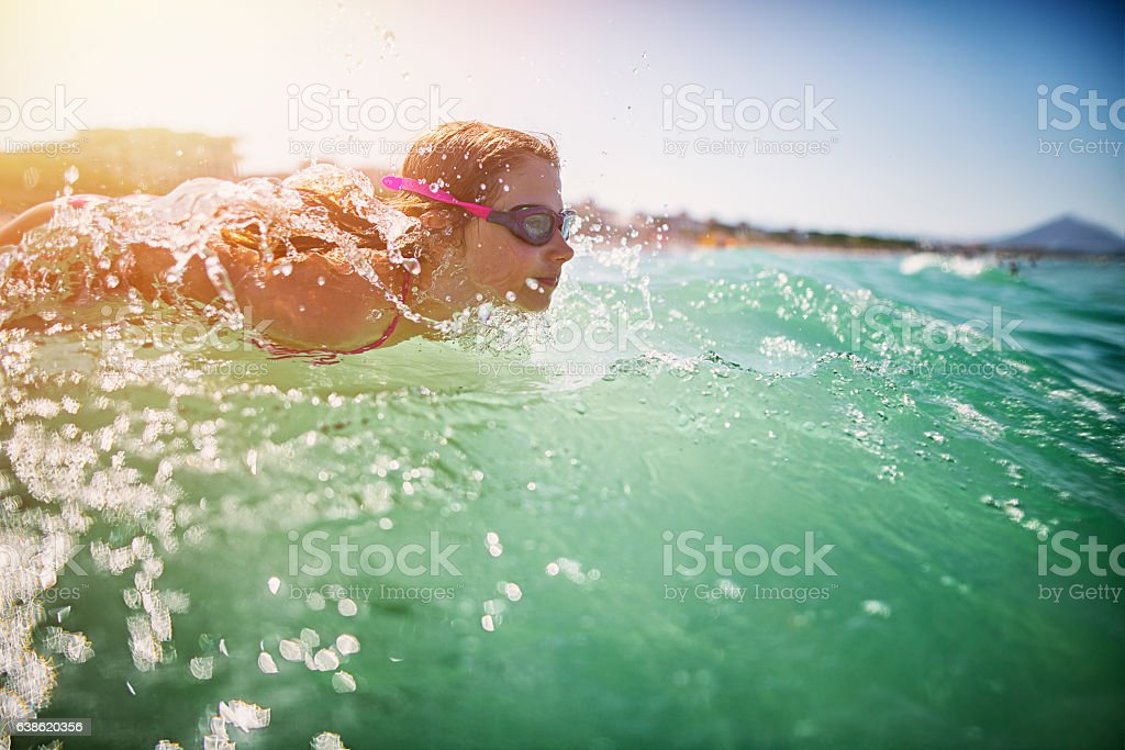 Little girl swimming in the sea stock photo