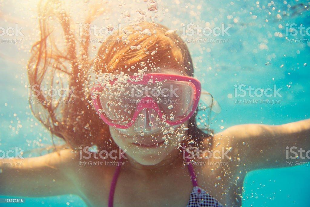 Little girl swimming underwater stock photo