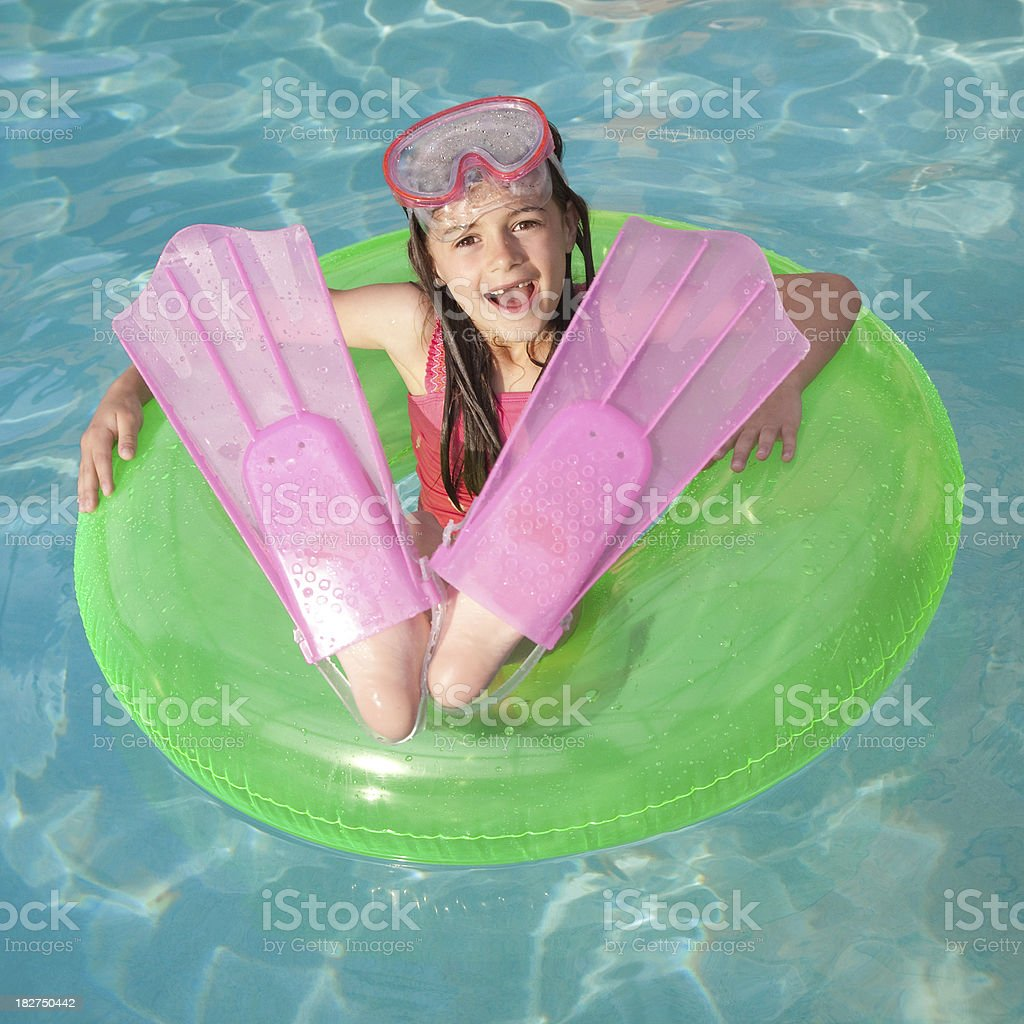 Little Girl Swimming with Inner Tube, Flippers, and Goggles royalty-free stock photo