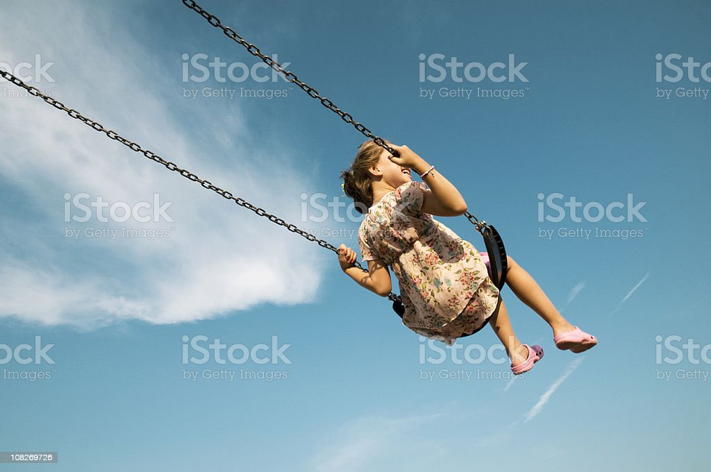 Little Girl Swinging Against Blue Sky stock photo