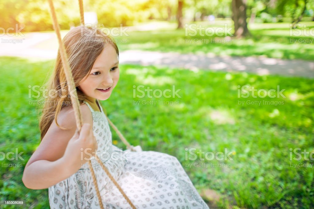 Little girl swinging in a park royalty-free stock photo