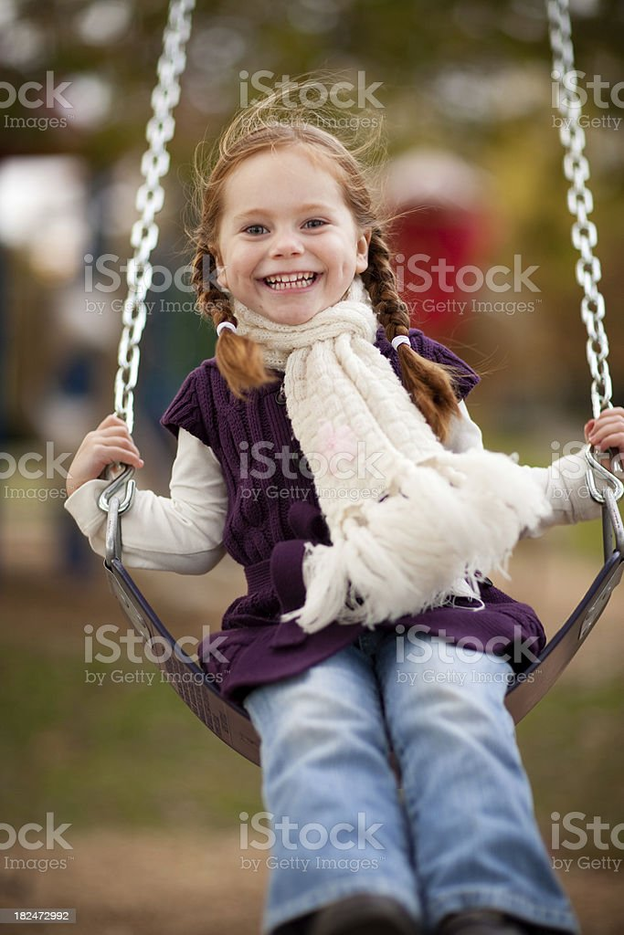 Little Girl Swinging in the Park on an Autumn Day royalty-free stock photo