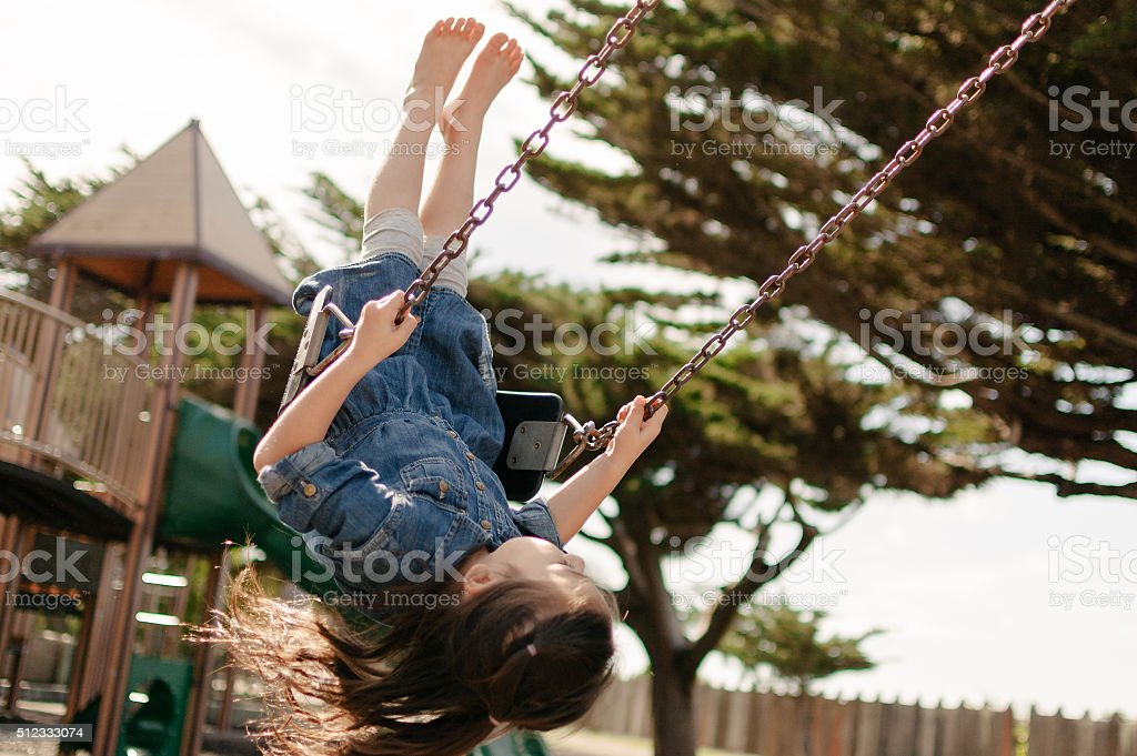 Little girl swinging on a swing in a playground stock photo