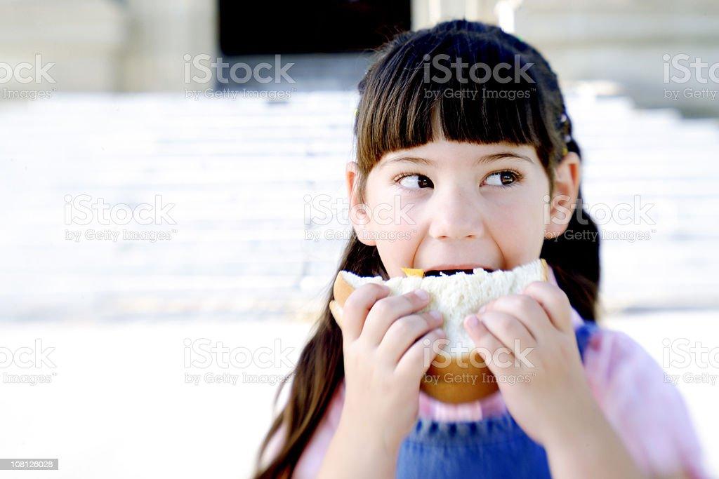Little Girl Taking Bite Out of Sandwich, Portrait stock photo