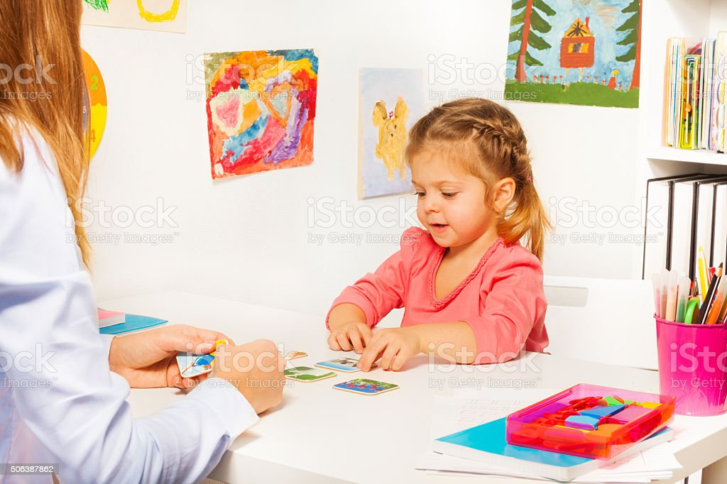 Little girl taking cards from table in the class stock photo