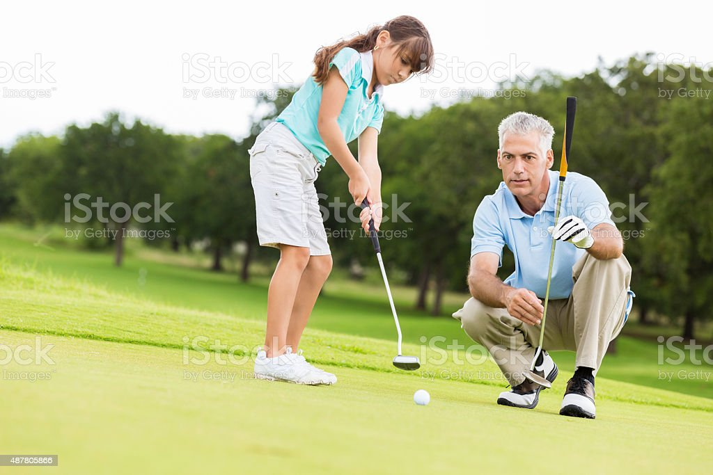 Little girl taking golf lesson from country club pro stock photo