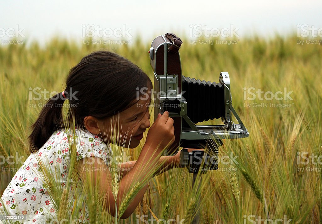 Little Girl Taking Photographs in Field with Vintage Camera royalty-free stock photo