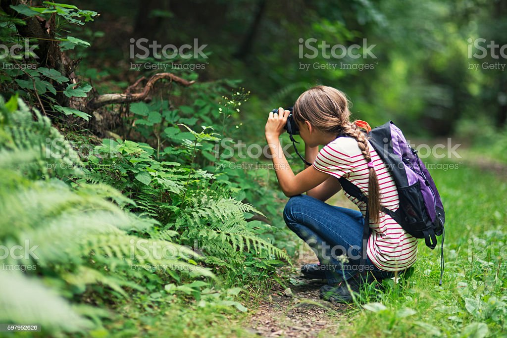 Little girl taking photos in the forest stock photo